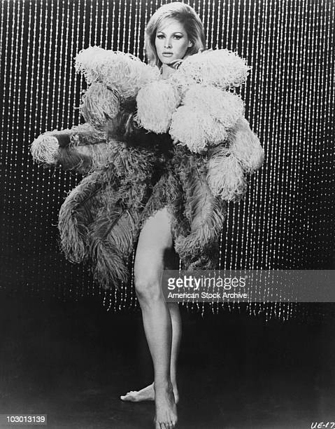 Actress Ursula Andress standing barefoot before a beaded curtain while covering her upper body with ostrich feathers circa 1965