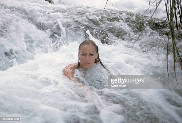 Actress Ursula Andress swims in a cascading stream Jamaica