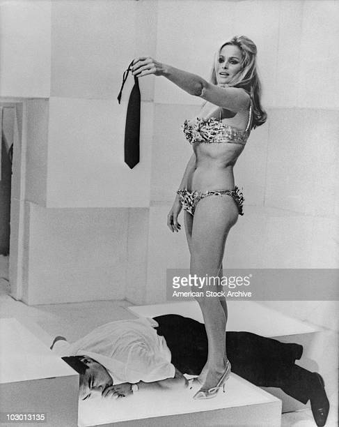 Actress Ursula Andress wearing a bikini and high heels while her outstretched hand holds a tie a man lies beneath her circa 1965