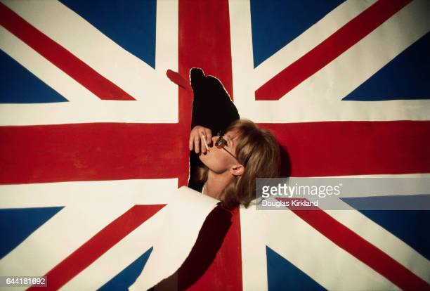 Actress Vanessa Redgrave smokes a cigarette through a rip in a Union Jack