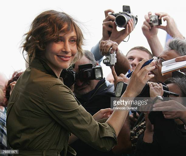 "Actress Vera Farmiga of the U.S. Signs autographs before attending a press conference for the film ""Never Forever"" during the 33rd Deauville American..."