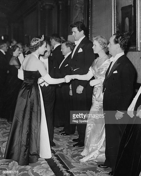Actress Veronica Hurst, with actor Rock Hudson on her right) being presented to Queen Elizabeth II at the Royal Film Performance in Leicester Square,...