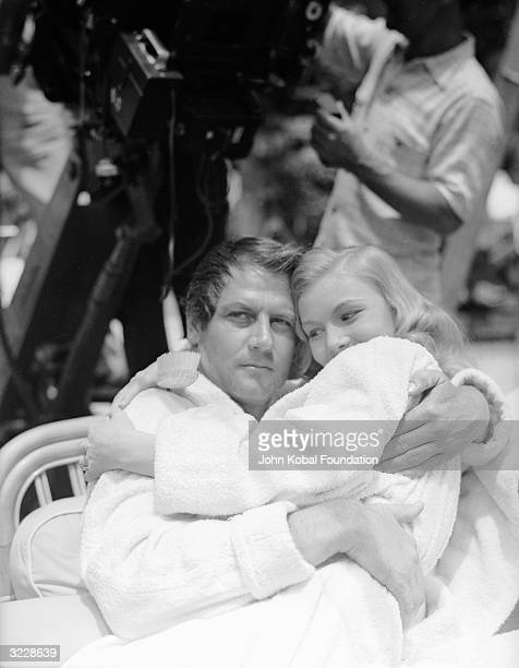 Actress Veronica Lake perches on the lap of her costar Joel McCrea on the set of 'Sullivan's Travels' directed by Preston Sturges