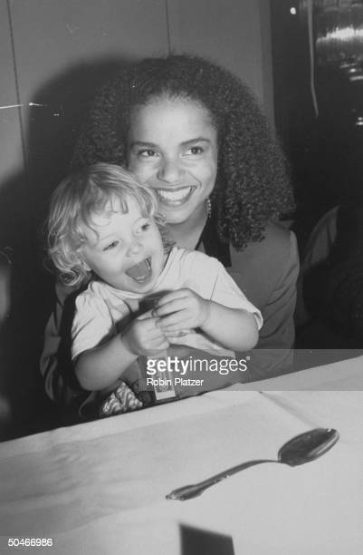 Actress Victoria Rowell star of TV soap The Young and the Restless holding young daughter Maya on her lap at premiere party for the newly restored...