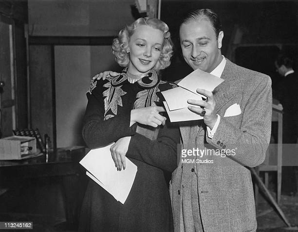 Actress Virginia Bruce reading her fan mail with film director Edwin Marin who directed her in the 1939 MGM film 'Society Lawyer'