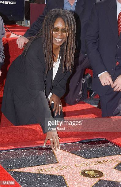 Actress Whoopi Goldberg touches the star she was honored with during a ceremony on the famous Hollywood Walk of Fame November 13 2001 in Hollywood CA...