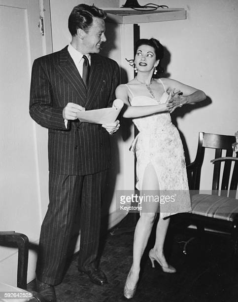 Actress Yvonne de Carlo being coached by actor Van Johnson as they prepare to appear at a charity fund raising event in Hollywood CA circa 1955
