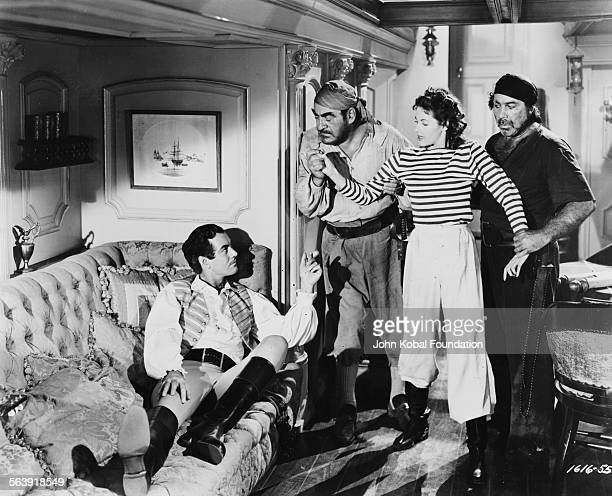 Actress Yvonne De Carlo being manhandled by two pirates in a scene from the film 'Buccaneer's Girl' for Universal Pictures 1950