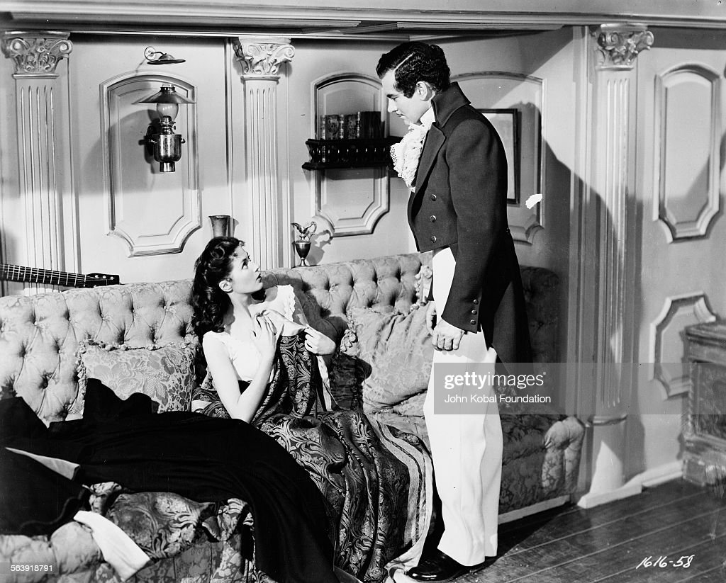 Actress Yvonne De Carlo (1922-2007) in a state of undress with another actor in a scene from the film 'Buccaneer's Girl', for Universal Pictures, 1950.