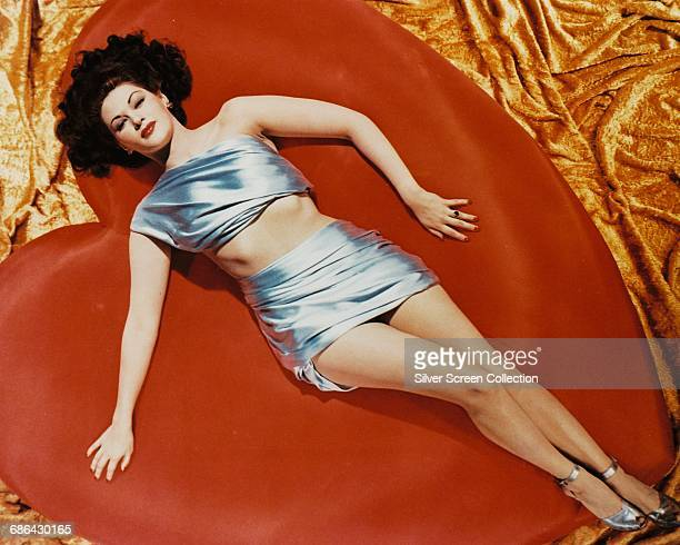 Actress Yvonne De Carlo lying on a giant red heart circa 1950
