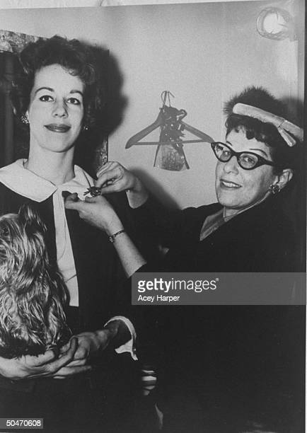 Actress/comedienne Carol Burnett getting pin put on her collar by photographer's assist Ray Hoffman during photo op years later Hoffman became victim...