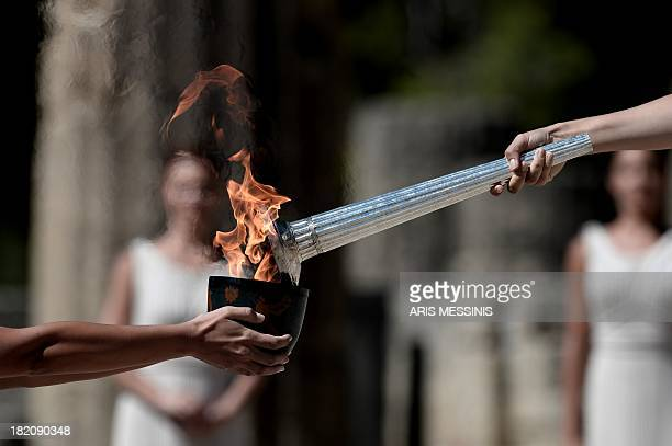 Actresses acting as high priestesses transfer the Olympic Flame into a pot on September 28 2013 in ancient Olympia the sanctuary where the Olympic...