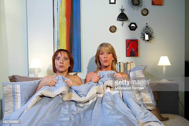 Actresses Alessia Marcuzzi and Debora Villa both halfdressed pose under the blanket during a photo shoot on the set of Vous les femmes in 2008 at...