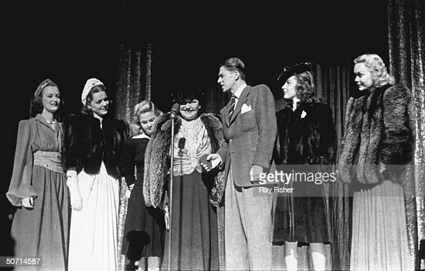 [LR] Actresses Arleen Whelan Joy Hodges June Preisser columnist Louella Parsons actor Ronald Reagan actresses Susan Hayward and Jane Wyman on stage...