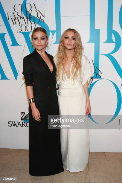 Actresses Ashley and Mary-Kate Olsen pose in the green room during the 25th Anniversary of the Annual CFDA Fashion Awards held at the New York Public...