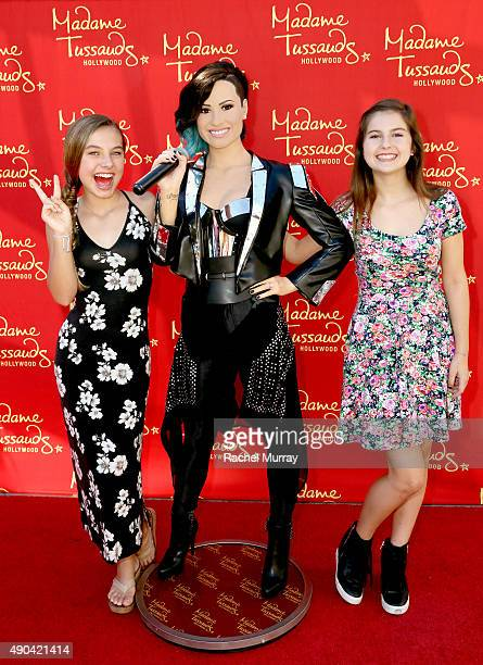 Actresses Caitlin Carmichael and Izzy Eggerling pose with the Demi Lovato Wax Figure during Merlin's Magic Wand Children's Charity and Madame...