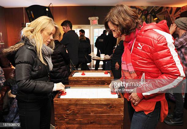 Actresses Cheryl Hines and Allison Janney enjoy a game of air hockey during Day 2 of the Puma Social Lounge at TMobile Google Music Village at The...