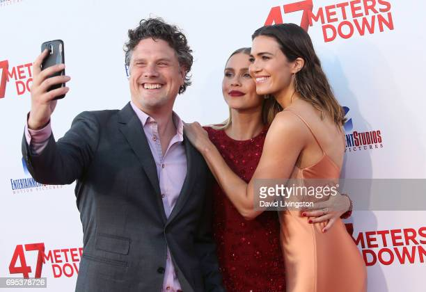 Actresses Claire Holt and Mandy Moore pose for a selfie with director Johannes Roberts at the premiere of Dimension Films' '47 Meters Down' at...