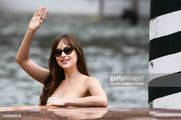 Actresses Dakota Johnson waves as she arrives by boat at the Excelsior Hotel's pier on September 1 2018 during the 75th Venice Film Festival at...