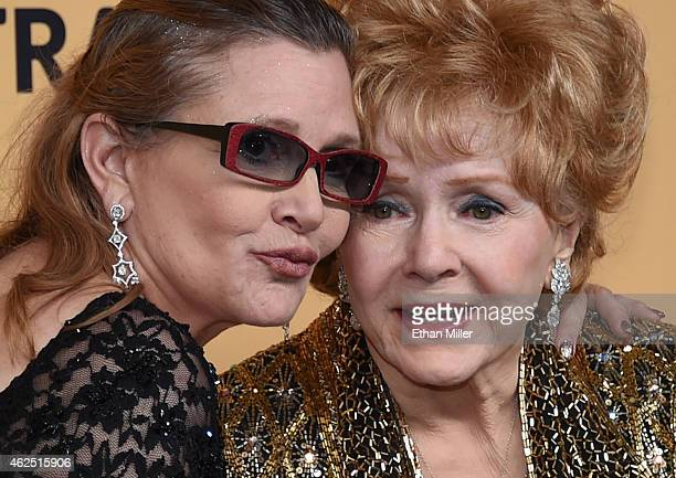 Actresses Debbie Reynolds recipient of the Screen Actors Guild Life Achievement Award and her daughter Carrie Fisher pose in the press room during...