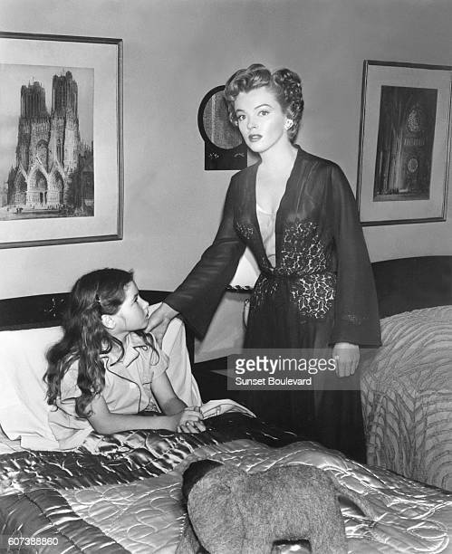 Actresses Donna Corcoran and Marilyn Monroe on the set of the 1952 film Don't Bother to Knock directed by Roy Ward Baker