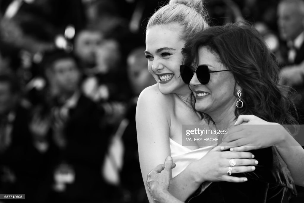 US actresses Elle Fanning (L) and Susan Sarandon pose as they arrive on May 17, 2017 for the screening of the film 'Ismael's Ghosts' (Les Fantomes d'Ismael) during the opening ceremony of the 70th edition of the Cannes Film Festival in Cannes, southern France. / AFP PHOTO / Valery HACHE