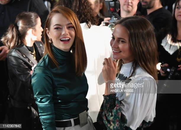 Actresses Emma Stone and Alicia Vikander talk during the Louis Vuitton Cruise 2020 Fashion Show at TWA Flight Center at JFK Airport on May 8, 2019 in...