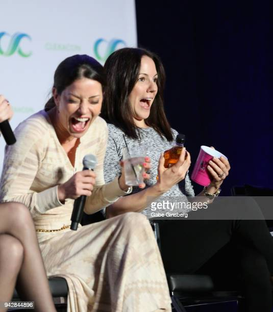 Actresses Emmanuelle Vaugier and Anna Silk react to Silk being handed a bottle of Jim Beam and a cup at the 'Lost Girl Reunion' panel during the...