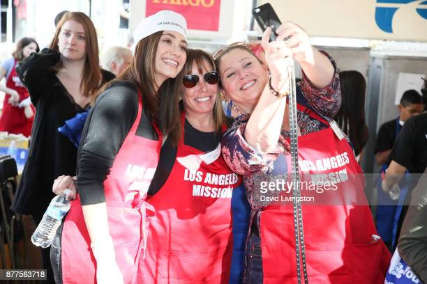 Actresses Emmy Rossum Melissa Rivers and Camryn Manheim are seen at the Los Angeles Mission Thanksgiving Meal for the homeless at the Los Angeles...
