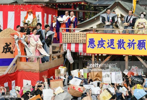 Actresses Erika Toda and Yuko Oshima scatter roasted beans during the annual Setsubun event marking the turn from winter to spring at Naritasan...