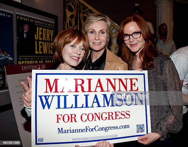 Actresses Frances Fisher Jane Lynch and Marcia Cross hold up a sign in support of Marianne Williamson at her campaign rally at Saban Theatre on May...