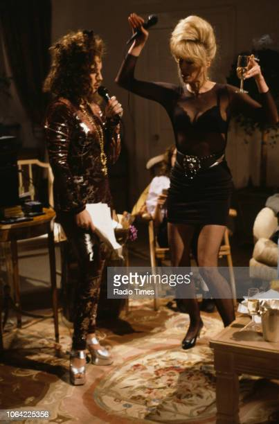 Actresses Jennifer Saunders and Joanna Lumley singing karaoke in a scene from episode 'Birthday' of the television sitcom 'Absolutely Fabulous',...