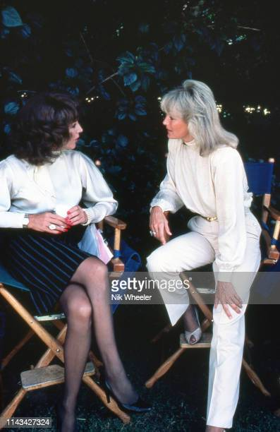 Actresses joan Collins and linda evans chat during break in filming on set of television hit show Dynasty in Hollywood circa 1984