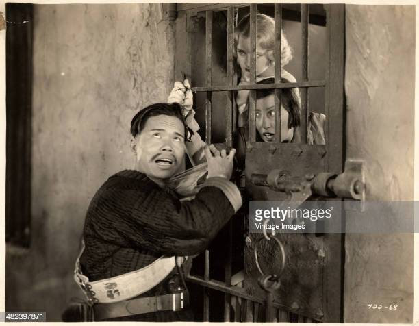 Actresses Josephine Dunn and Polly Moran assault their Asian gaoler in a scene from the MGM film 'China Bound' 1929