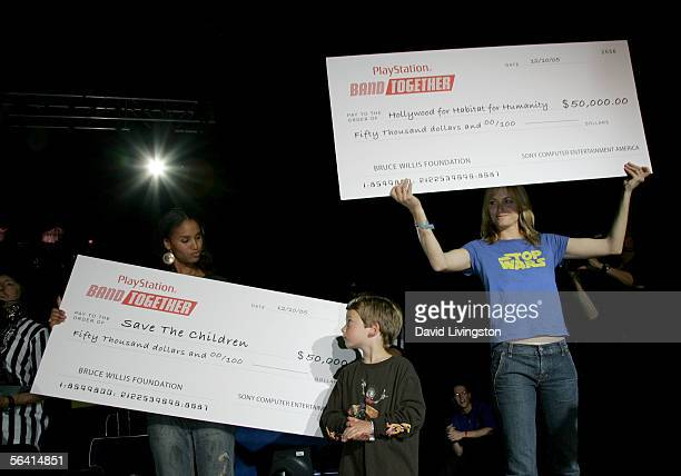 Actresses Joy Bryant Amber Valletta and son Auden McCaw present a check during Playstation BANDtogether a benefit presented by Sony Computer...