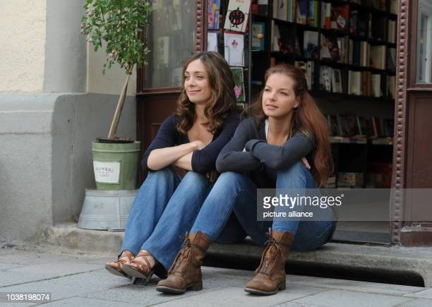 Actresses Julia Richter and Yvonne Catterfeld sit outside of the entrance to a bookstore during filming for the movie 'Cecelia Ahern' in...
