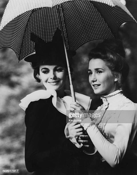 Actresses Juliette Villard and Brigitte Fossey sharing an umbrella on the set of the film 'Le Grand Meaulnes' circa 1967