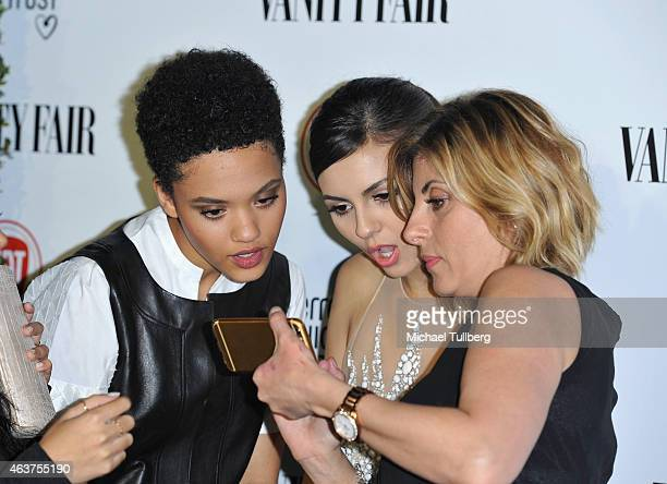 Actresses Kiersey Clemons and Victoria Justice and guest look at a cell phone at the Vanity Fair And Fiat Toast To Young Hollywood in support of the...
