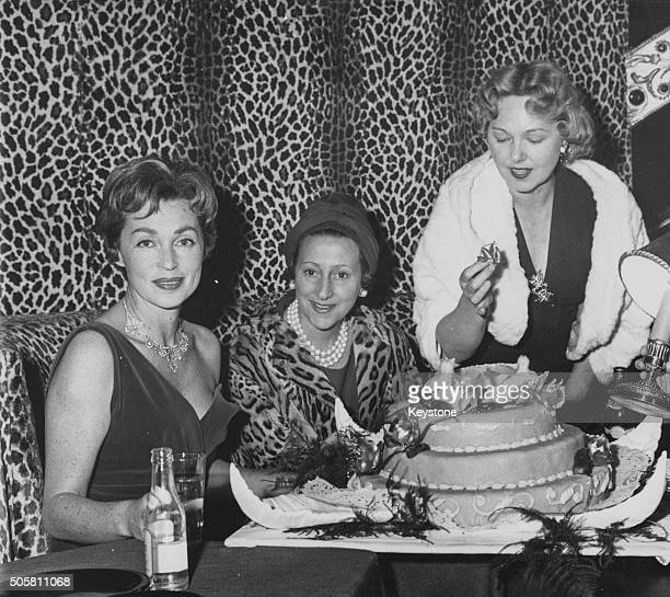 Actresses Lilli Palmer Blanche Montel and Paulette Dubost sitting next to a celebration cake at a cocktail party following the premiere of the film...