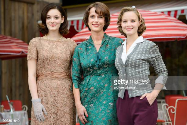 Actresses Maria Ehrich Claudia Michelsen and Emilia Schule standing together for a joint portrait on the set of the ZDF series 'Ku'damm 59' in Berlin...