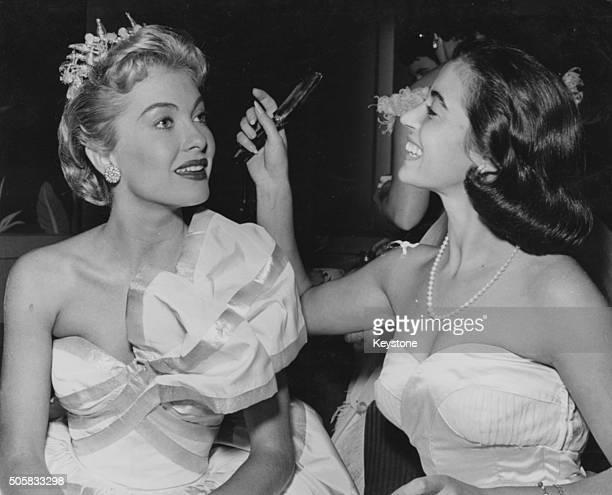 Actresses Marisa Pavan and Lori Nelson checking their hair and makeup before the Hollywood MakeUp Artists Ball California circa 1963