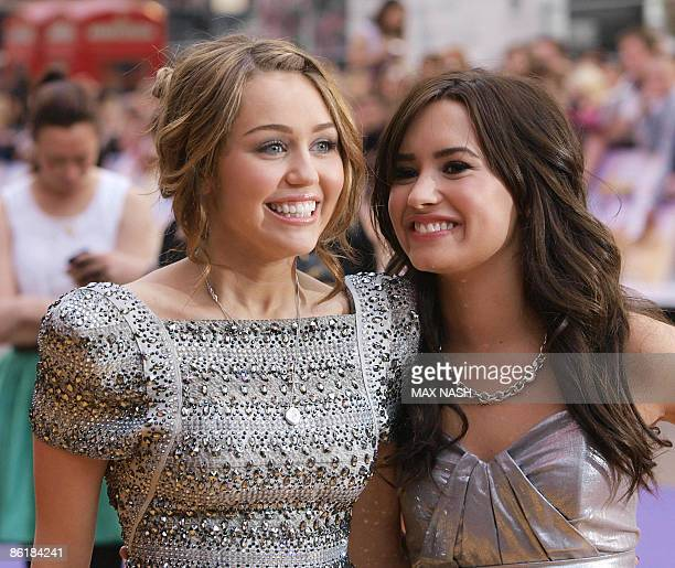 US actresses Miley Cyrus and Demi Lovato greet each other after arriving in London's Leicester Square on April 23 to attend the British Premiere of...