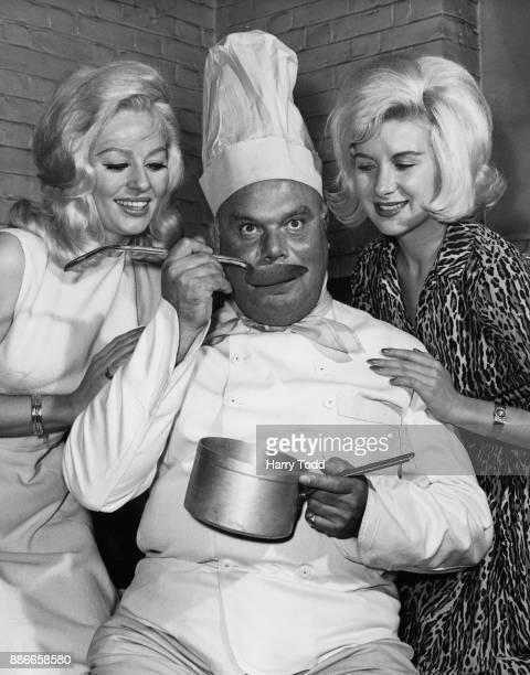 Actresses Sheree Winton and Caron Gardner watch actor Peter Bull sample his own cooking during rehearsals for the BBC television play 'The Big Eat'...