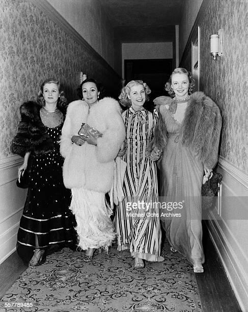 Actresses Virginia Bruce Dolores del Rio Anita Louise Virginia Bruce walk down a hallway to a party in Los Angeles California