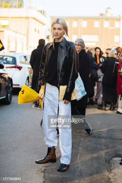 Actress/Model Hunter Schafer wears a black leather jacket white pants black and brown boots and carries a bouquet of flowers after attending the...