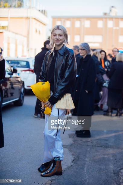 Actress/Model Hunter Schafer wears a brorwn leather jacket holds a bouquet of flowers white pants and brown boots after the Marni show during Milan...