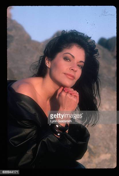Actress/singer Appolonia is shown seated outdoors near a large rock formation She wears a black leather jacket around her bare shoulders Undated
