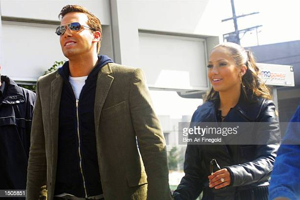 Actress/singer Jennifer Lopez and actor Ben Affleck hold hands while filming her new music video at Barefoot restaurant on October 20, 2002 in...