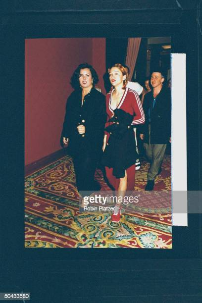 Actress/singer Madonna wearing lowcut maroon cotton adidas dress w a sideslit matching platform Puma sneakers arriving w actress Rosie O'Donnell at...