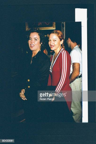 Actress/singer Madonna wearing lowcut maroon cotton adidas dress posing w actress Rosie O'Donnell at the premiere party for the film Sleepless in...